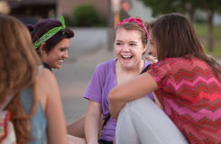 Four Teen Girls Giggling. Mixed group of four teenage girls outside giggling Stock Photo