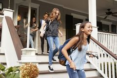 Four teen girls leaving house with school bags royalty free stock photography