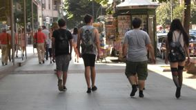 Four teenage boys walking down the street of a city in the middle of the people. royalty free stock image