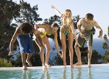 Four teenage friends having fun in a swimming pool Stock Image
