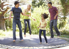 Four Teenage Friends Jumping On Trampoline In Garden Stock Photography