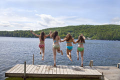 Four teenage girls jumping off dock at lake. Four teenage girls jumping off a dock at a lake, holding hands.  All are wearing colorful two-piece bathing suits Royalty Free Stock Image