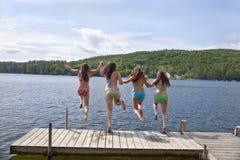 Four teenage girls jumping off dock at lake royalty free stock image