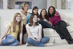 Four teenage girls with mothers watching television Stock Photo