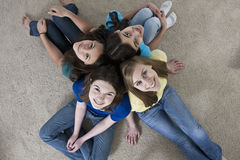 Four teenage girls sitting back to back  Stock Images