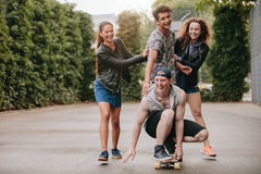 Four teenagers enjoying outdoors with skateboard Royalty Free Stock Image