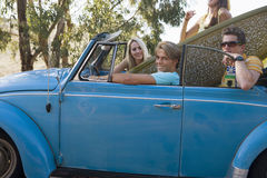 Four teenagers (17-19) sitting in blue convertible car with surfboard, portrait, side view Stock Images