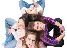 Four teenagers sitting on white with cellphones. Four young people sitting on a white floor, shot from above, looking up, smiling very cheerfully Stock Photo