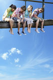 Four teenagers sitting on wooden bridge against blue sky Royalty Free Stock Photo