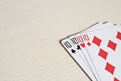 Four ten poker hands playing cards on a light desk background. Game luck abstract. Gambling game for people. Copyspace Stock Image