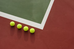 Four tennis balls on the court Royalty Free Stock Image