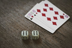 Four tens on a wooden table. concept of gambling and place for your text. Playing cards and two dice number double six closeup stock image