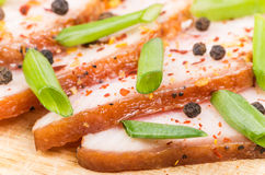 Four thin slices of bacon, onion and pepper on wooden board Royalty Free Stock Image