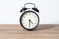 It is four thirty o`clock. The time is 4:30 am or pm. The time is 4:30 o`clock. A retro clock isolated on a wooden table and white background Stock Photo