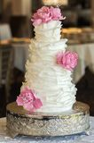 Four tier wedding cake with fondant ruffles and pink edible roses. Displayed in a elegant ballroom on a round silver cake stand Royalty Free Stock Image
