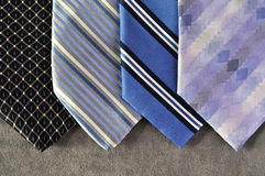 Four ties in blue tones with a gray background. Four ties in blue, white, purple, light blue and dark blue tones and stripes, on a gray background Stock Photography