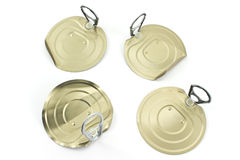 Four tin can lids with opener Stock Photo