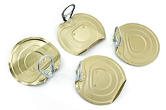 Four tin can lids with opener Royalty Free Stock Photos