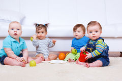 Four toddlers. Sit on the carpet Stock Photography