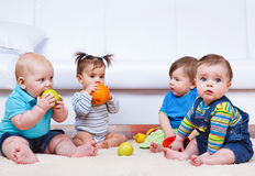 Four toddlers. Sitting in a lounge Stock Photo