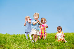 Four toddlers. On the grass against blue sky Stock Images