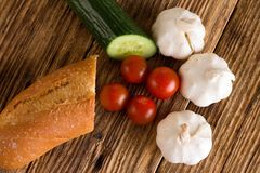 Four tomatoes among garlic cucumber and baguette Stock Photography