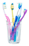 Four toothbrushes and interdental brush in glass Royalty Free Stock Image