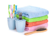 Four toothbrushes, liquid soap, hairbrush and colorful towels Royalty Free Stock Photo