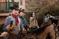 Four Tough Western Robbers. Cowgirl with three male companions in old American west scene Stock Photo
