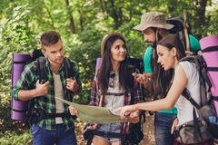 Four tourists got lost in the forest, holding map, trying to fin. D the way, disscus it, all having backpacks, mates, all needed for overnight stay Stock Photography