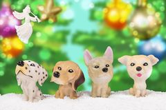 Four toy dogs in the snow. Four small dogs on white snow with blurred colorful background with Christmas toys and an angel Stock Image