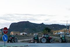 Four tractors with the mountain in the background royalty free stock image