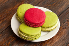 Four traditional french colorful macarons on plate, wooden background Royalty Free Stock Images