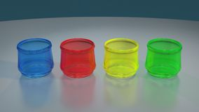 FOUR COLORED GLASSES ON REFLECTIVE TABLE. Four transparent colored glasses in a line over a reflective table Stock Photos
