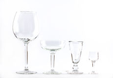 Four transparent elegant crystal glasses for cocktails lined next to each other on a white background.  Stock Photos
