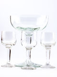 Four transparent elegant crystal glasses for cocktails on a white background Royalty Free Stock Photography