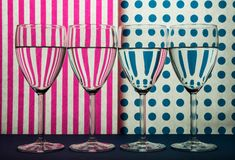 Four transparent glasses for wine standing in line and white background with pink stripes and blue spots. Four transparent wine glasses standing in line on the royalty free stock photos