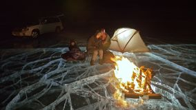 Four travelers by fire right on ice at night. Campground on ice. Tent stands next to fire. People are warming around. Four travelers by fire right on ice at stock footage