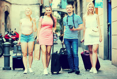 Four travelling people with bags Stock Photo