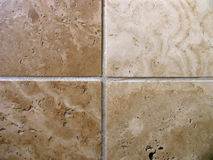 Four travertine tiles. Travertine flooring tiles showing natural differences in colour and pattern royalty free stock images
