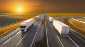 Four trucks in motion blur on the empty highway at sunset Stock Image