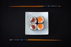 Four tuna salmon maki sushi and chopstick on black Stock Photography