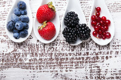 Four types of berries in a spoons Royalty Free Stock Photo
