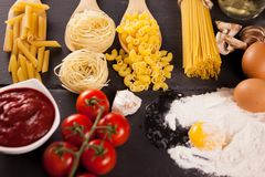 Four types of raw uncooked pasta next to tomatoe souce. Healthy and delicious food - Four types of raw uncooked pasta next to tomatoe souce, fresh tomatoes royalty free stock photography