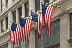 Four U.S. Flags waving mounted to an office building in New York City stock photography