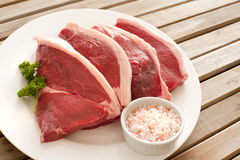 Four uncooked succulent beef steaks Stock Image