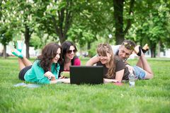 Four university students comparing their notes Stock Photos