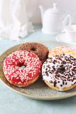 Four variegated sweet donuts for breakfast and teapot Stock Photo