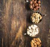 Four vintage cupro-nickel cup full of different nuts, almonds, pistachios, walnuts and hazelnuts on a dark wooden Royalty Free Stock Photo
