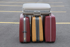 Four vintage suitcases on a parking lot stock photos
